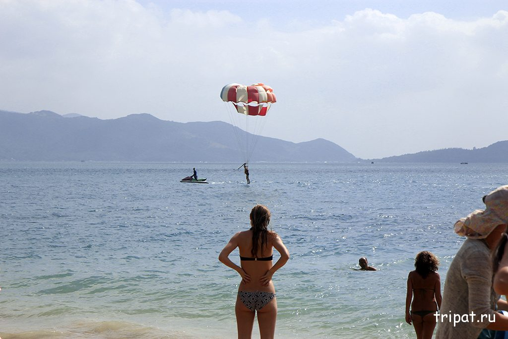 Девушка на пляже наблюдает за полетом